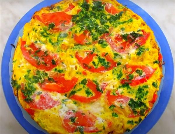 омлет с луком и помидорами на сковороде